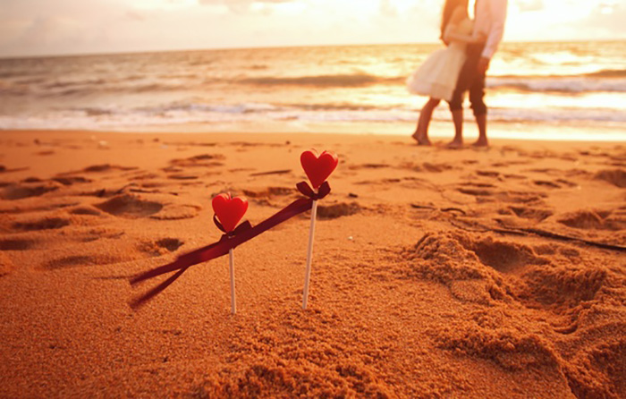 Пляж, сердечки, влюбленные на фоне заката